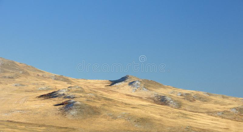 Winter landscape with a smooth hills covered with a yellow dry grass and first snow under dark blue sky. In Khakassia, Russia royalty free stock photos
