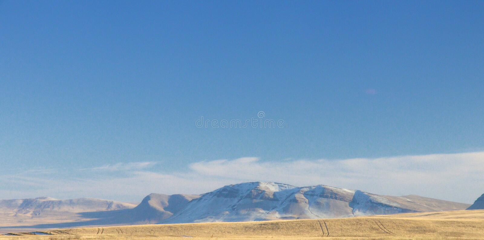 Winter landscape with a smooth hills covered with a yellow dry grass and snow under dark blue sky. In Khakassia, Russia stock photography