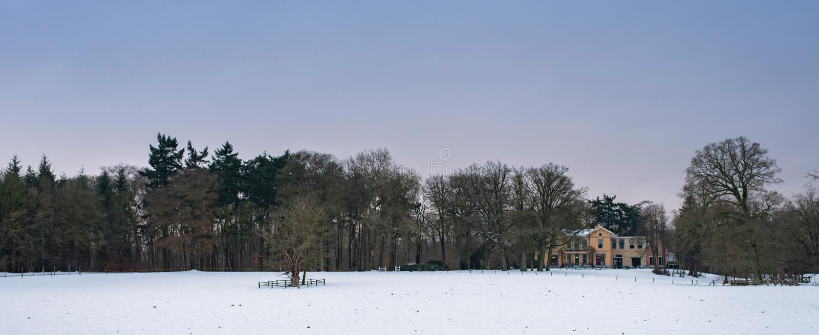 Winter landscape in snow with bare trees and country manor house. royalty free stock images