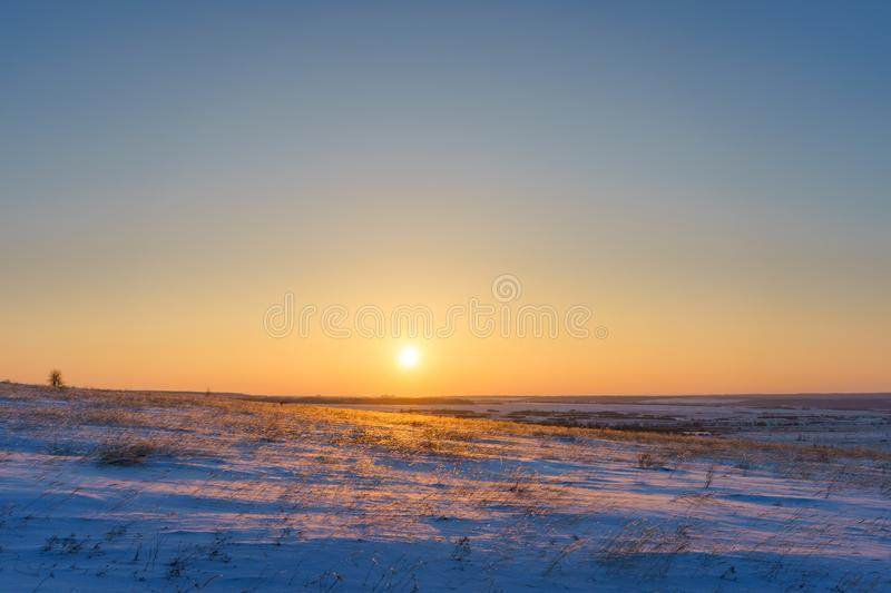 Winter landscape with snow covered plain, blue sky and orange su. N at sunset. Beautiful natural scenic background royalty free stock photos