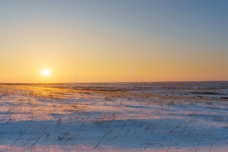 Winter landscape with snow covered plain, blue sky and orange su. N at sunset. Beautiful natural scenic background royalty free stock photography