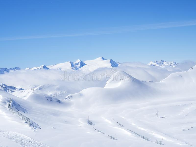 Winter landscape with snow covered slopes and blue sky, view from the top of Kitzsteinhorn mountain on . Kaprun ski. Resort, National Park Hohe Tauern, Austrian stock photography