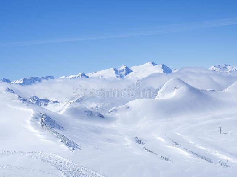 Winter landscape with snow covered slopes and blue sky, view from the top of Kitzsteinhorn mountain on . Kaprun ski. Resort, National Park Hohe Tauern, Austrian stock image
