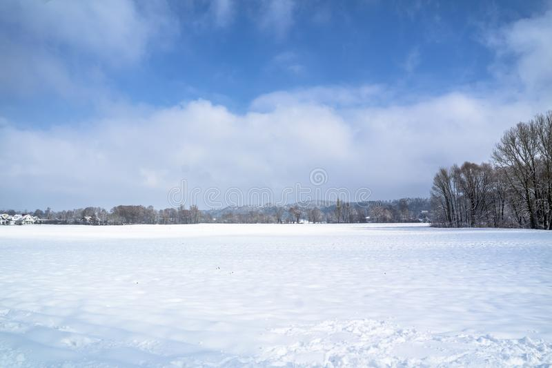 Winter landscape with snow field in countryside and trees and hills on horizon royalty free stock photos