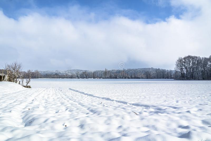 Winter landscape with snow field in countryside and trees and hills on horizon royalty free stock photography