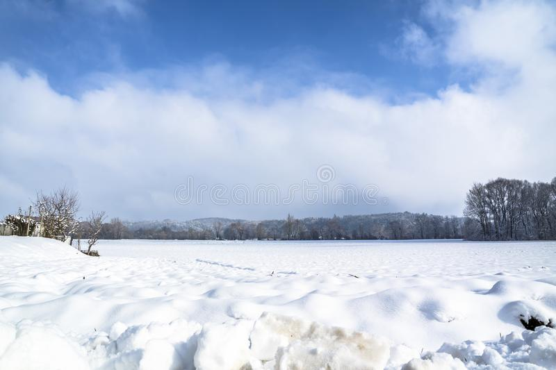 Winter landscape with snow field in countryside and trees and hills on horizon stock photos