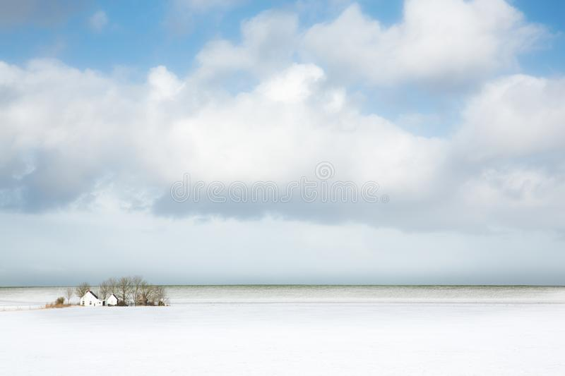 Winter landscape with snow in the fields and a lone farm in the background and a big sky. The Netherlands stock images