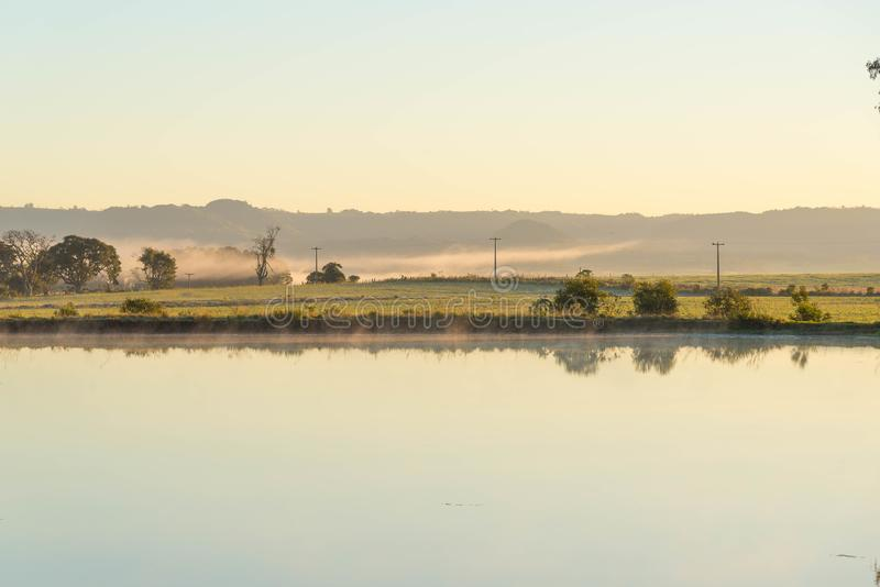 The pond and the winter Dawn. Winter landscape in southern Brazil. A pond and the horizon in the background, where electric power poles appear. Countryside royalty free stock photo