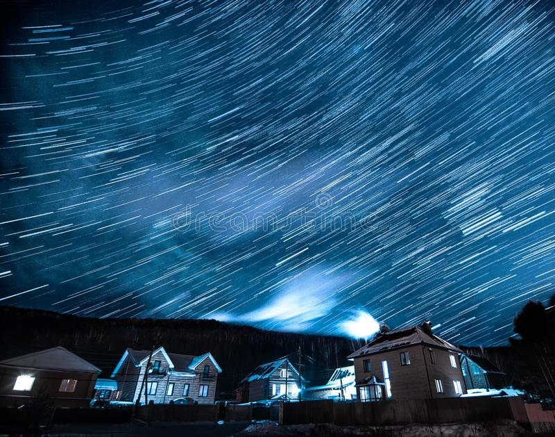 Winter landscape with star trails above houses and forest at night royalty free stock photos