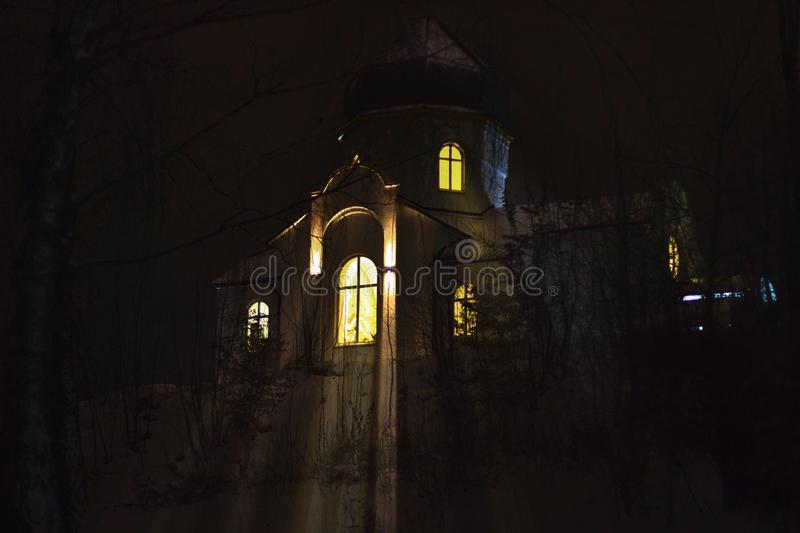 Winter landscape. Temple in the evening with light in the windows.  royalty free stock image
