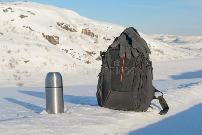 Winter landscape,thermos, and backpack are on the snow . royalty free stock image