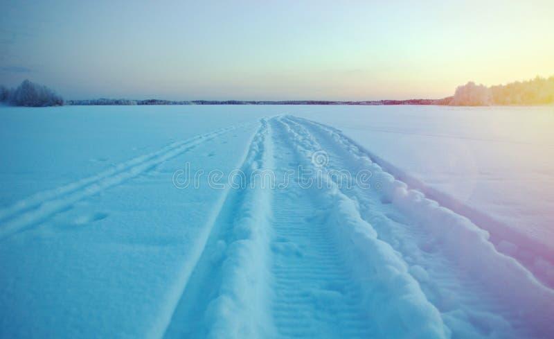 Winter frozen lake. Winter landscape.trace of a snowmobile on frozen lake stock photos
