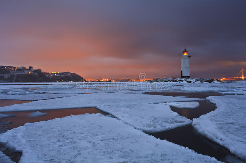 Winter landscape with a view of the lighthouse, iced sea and night city lights royalty free stock photography