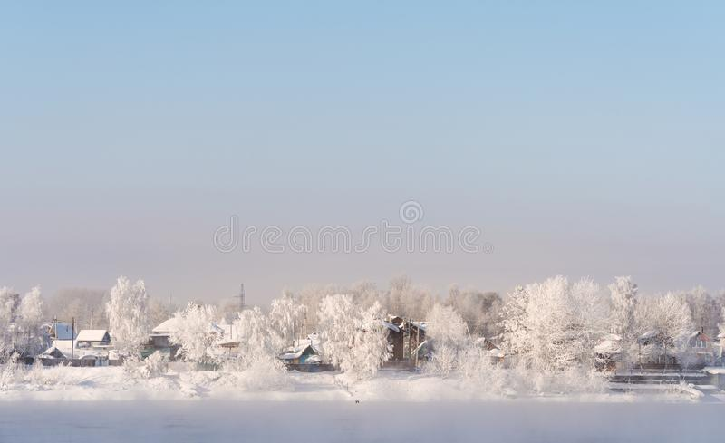 Winter landscape, white snow covered on trees and local houses in urban countryside, in Russia stock images
