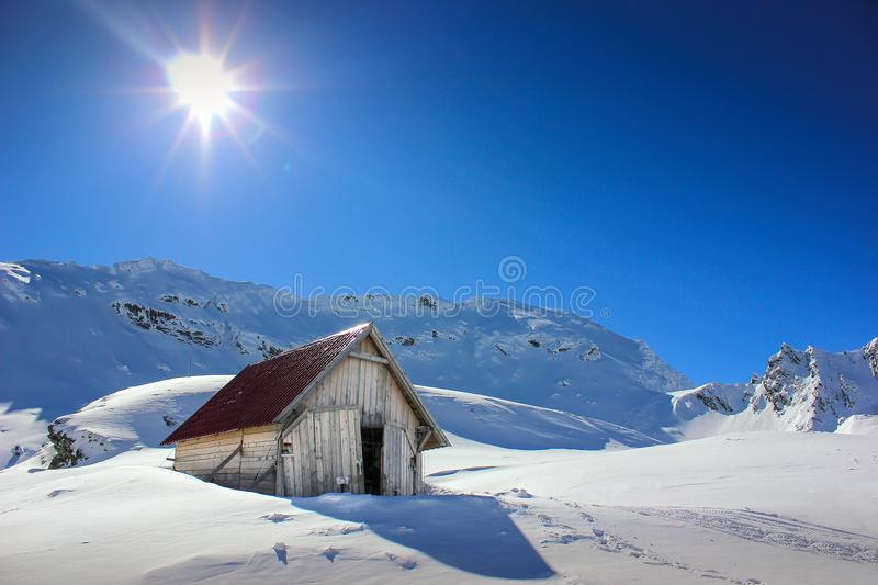 Winter landscape with wooden toolshed at Balea lake, Sibiu county, Romania. Winter landscape with wooden toolshed and Fagaras Mountains covered in thick layer stock photography