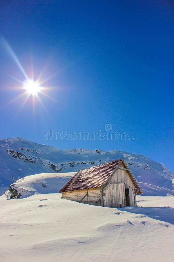 Winter landscape with wooden toolshed at Balea lake, Sibiu county, Romania. Winter landscape with wooden toolshed and Fagaras Mountains covered in thick layer stock image