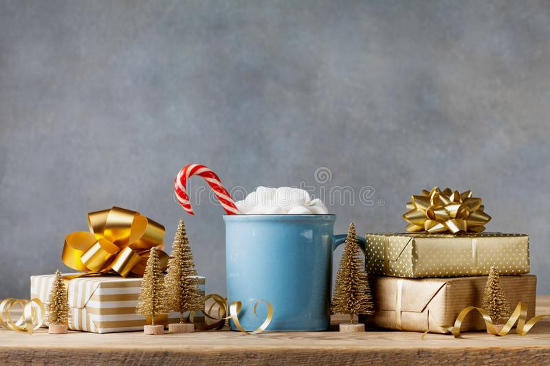 Winter lifestyle with cup of hot cocoa with marshmallows and Christmas gift or present boxes and holiday decorations. Winter lifestyle with cup of hot cocoa royalty free stock photography