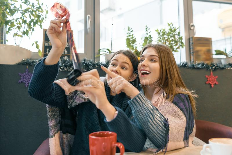 Winter lifestyle girls in cafe having fun looking at old film rolls stock image