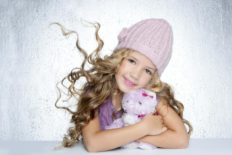 Winter little girl hug teddy bear smiling. Winter fashion cap little girl hug teddy bear smiling silver background stock image