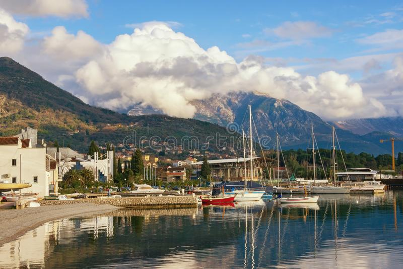 Winter Mediterranean landscape with white cloud on top of mountains. Montenegro, view of port in Tivat city. Winter Mediterranean landscape with a white cloud on royalty free stock photography