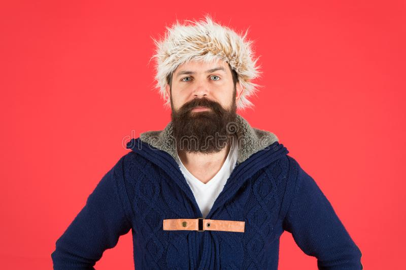 Winter menswear. Clothes design. Man bearded stand warm jumper and hat on red background. Winter season menswear stock photo