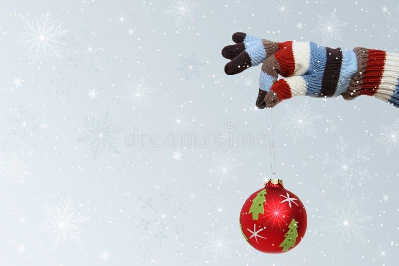 Winter mitten with Christmas ball. Winter mitten holding a Christmas ball stock photos