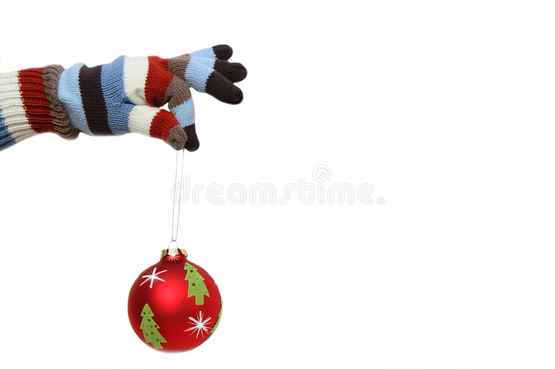 Winter mitten with Christmas ball. Winter mitten holding a Christmas ball royalty free stock photo