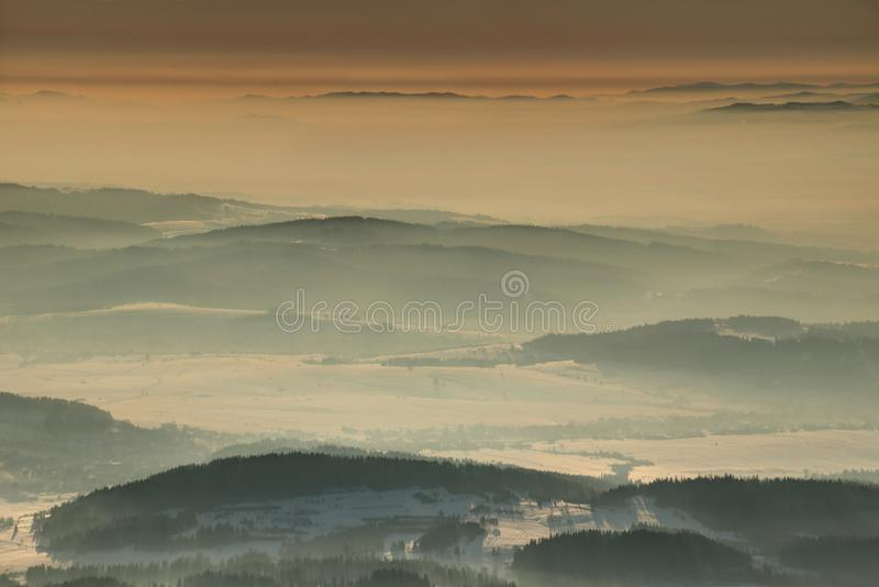 Winter morning light over rounded hills of Beskids range Poland. Red winter morning light over rounded hills of Beskid Orawsko Podhalanski range and hazy Dunajec stock photography
