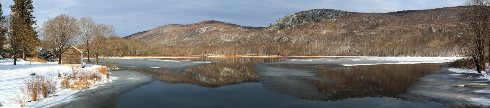 Winter mountain lake scene with cabin in Berkshires stock photography