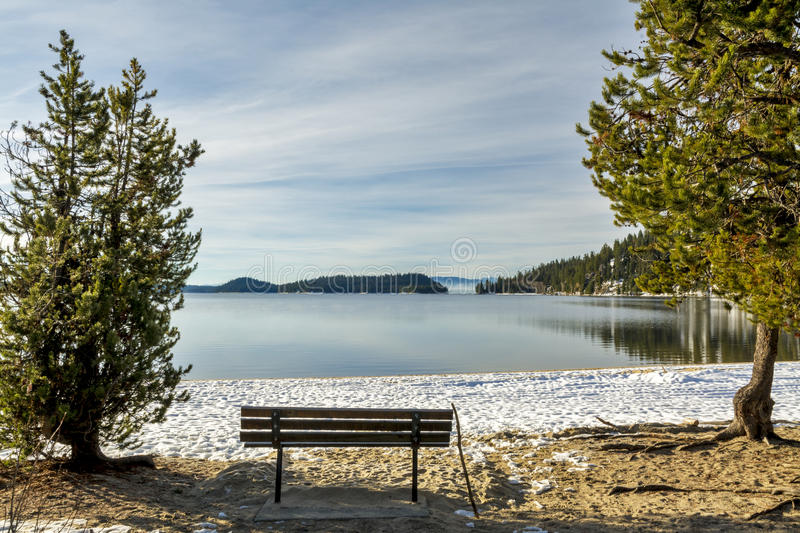Winter mountain lake with a sitting bench. Cold winter monring with a bench on the shore of a lake stock image