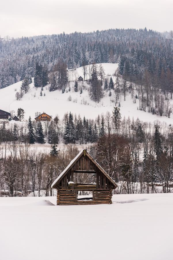 Winter mountain landscape in Alps. Wooden shed in the foreground. Mountain with trees and few houses in the background. Wooden shed in the foreground. Mountain royalty free stock photos