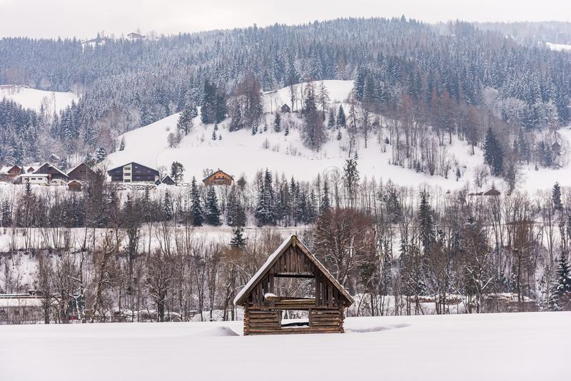 Winter mountain landscape in Alps. Wooden shed in the foreground. Mountain with trees and few houses in the background. Wooden shed in the foreground. Mountain royalty free stock image