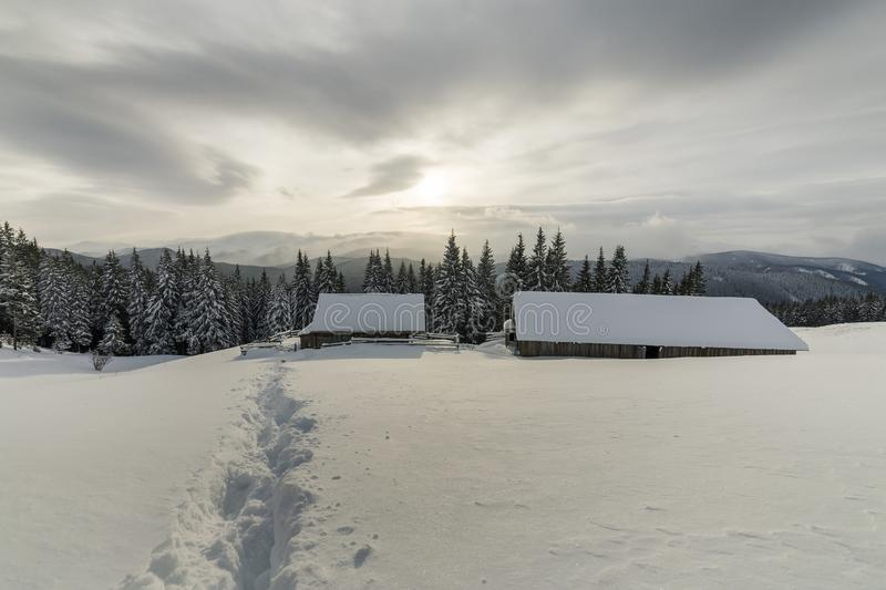 Winter mountain landscape. Old wooden houses on snowy clearing on background of mountain ridge, spruce forest and cloudy sky. Happy New Year and Merry royalty free stock images