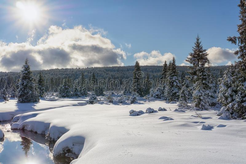 Winter mountain landscape with stream and wooden bridge stock photography