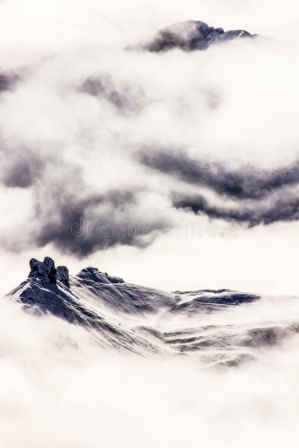 Winter mountain peaks in the foggy clouds, Minimalistic, Dolomites, Italy. Winter mountain peaks in the foggy clouds, Minimalistic in Dolomites, Italy royalty free stock photos