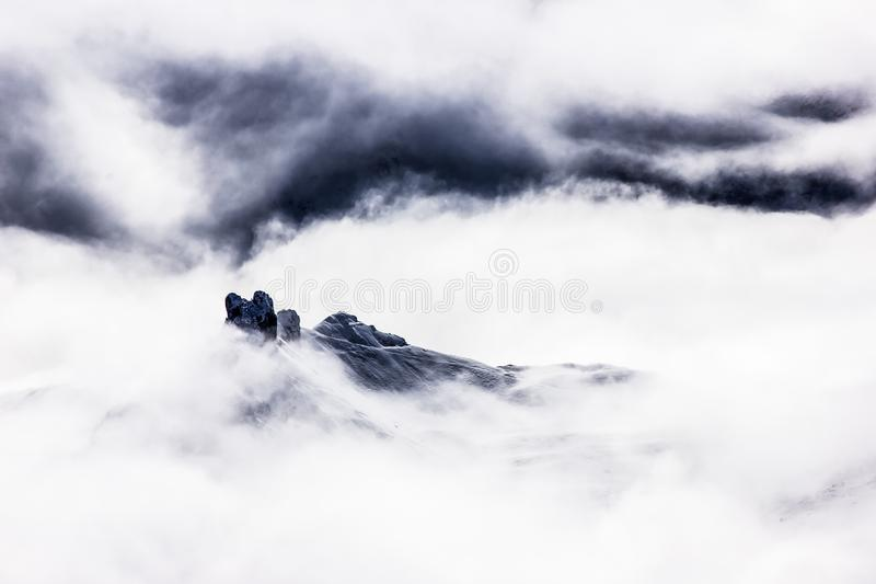 Winter mountain peaks in the foggy clouds, Minimalistic, Dolomites, Italy. Winter mountain peaks in the foggy clouds, Minimalistic in Dolomites, Italy royalty free stock images