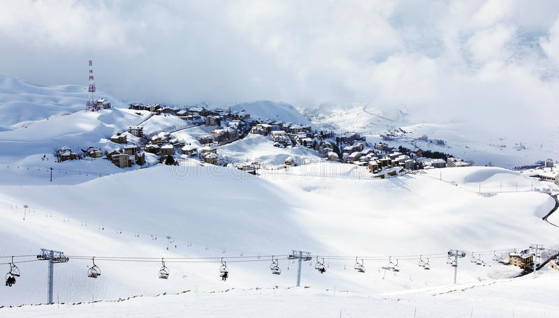 Winter mountain ski resort. Landscape with snow and cute little houses, chairlift with people playing sport stock photography