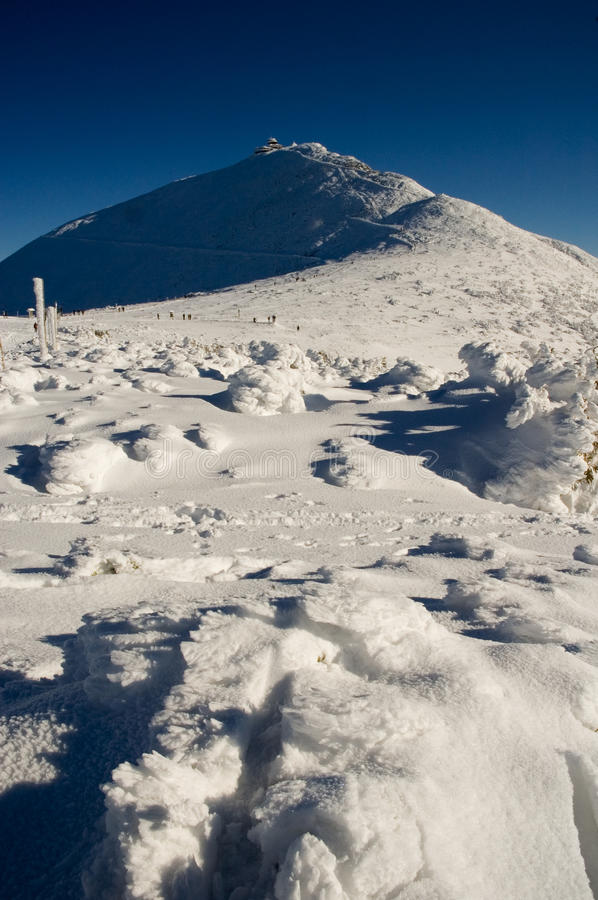 Winter mountain summit. Mountain summit Snezka in Giant mountains, Czech (Poland). Nice winter day, blue sky on the background and lot of snow on the foreground stock photo