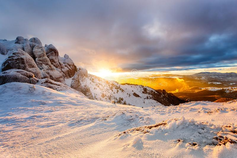 Winter mountain Sunset. Beautiful winter landscape at sunset with clouds and snow over the mountain cliffs royalty free stock image
