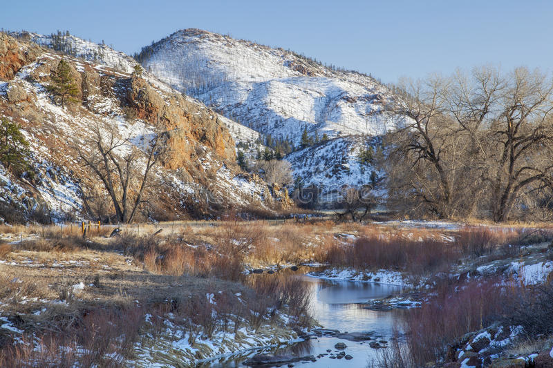 Winter in mountain valley. In COlorado Rocky Mountains, with burned forest on slopes and North Fork of Cache la Poudre River stock photo