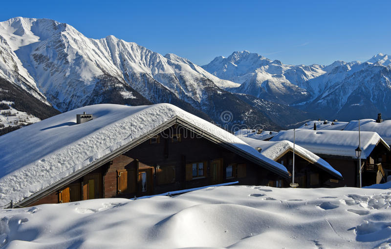 Winter in a mountain village. Snow-covered mountain peaks and chalets during winter in the mountain village Bettmeralp, Valais, Switzerland royalty free stock photography