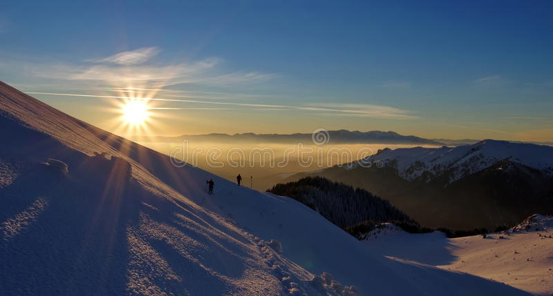 Splendid sunset. Winter mountain landscape. Sun, snow and hikers at high altitude - Ciucas Mountains, landmark attraction, Romania. Winter mountain landscape stock photography