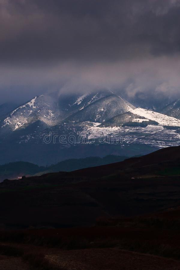 Winter mountains landscape with dramatic storm clouds, light in the dark shining on the snow mountain. Yunnan, South China stock images