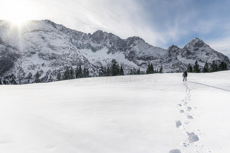 Winter mountains and man walking through snow. Footsteps in snow stock photo