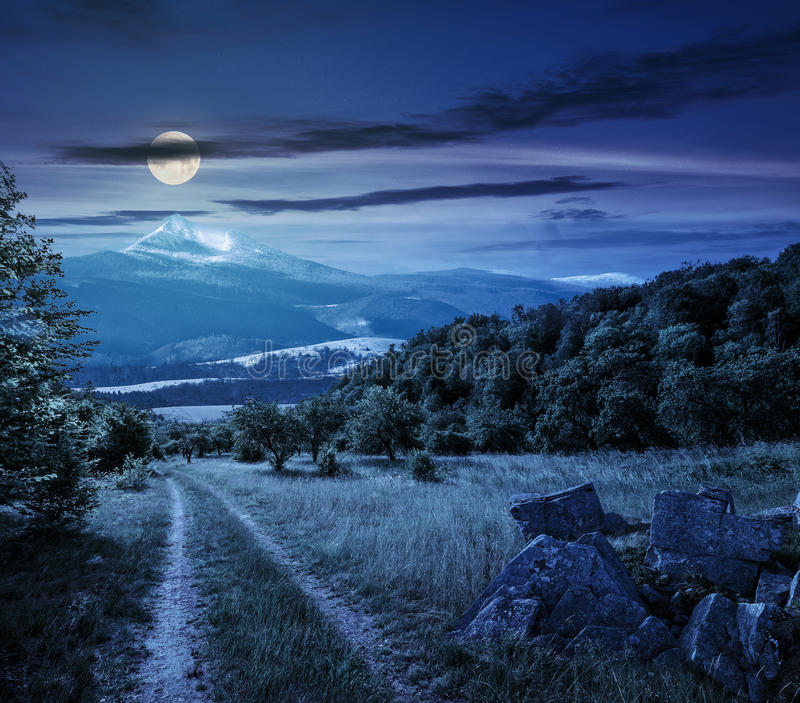 Winter in mountains meets spring in valley at night. Winter meets spring composite landscape. Valley with trees and boulders on a grass. Road through meadow goes royalty free stock photography