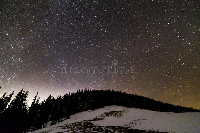 Winter mountains night landscape panorama. Milky Way bright constellation in dark blue starry sky over dark spruce pine trees stock photography