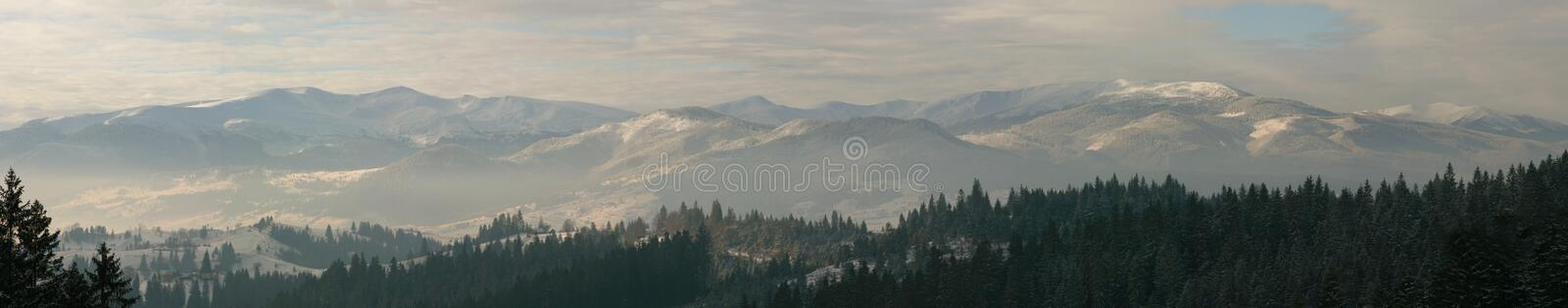 Winter mountains panorama. Panorama of snow covered mountains and dramatic clouds. Carpathians, Yablunitsky pass, Ukraine stock photography