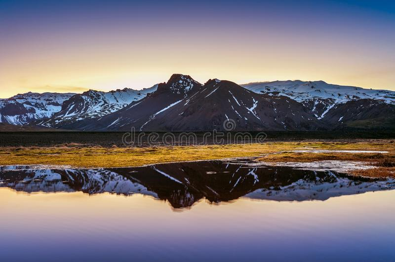 Winter mountains reflection at sunset in a lake.  stock image