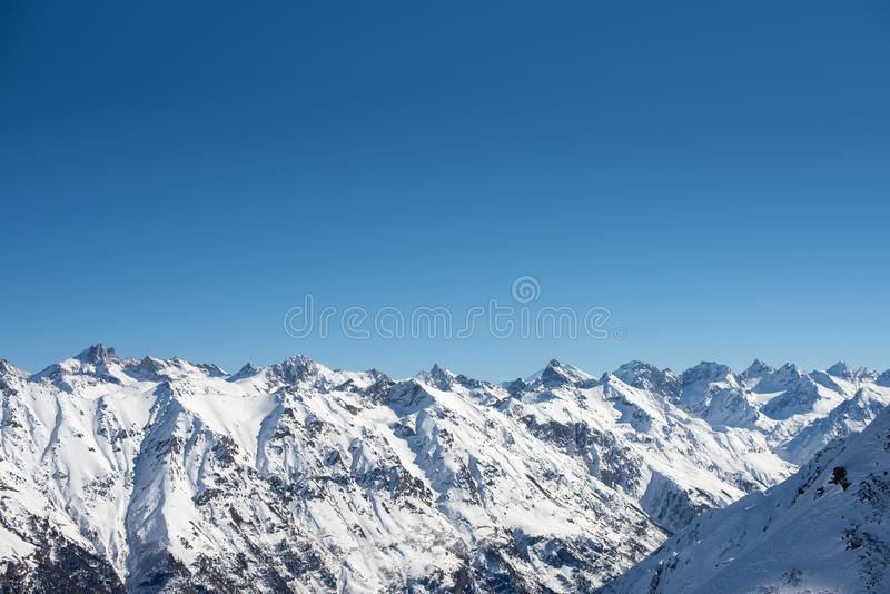 Winter mountains with snow and blue sky in nice sun day. Ski resort, sport concept. Caucasus Mountains, region Dombay. Wallpaper, banner, background, deep blue royalty free stock photo