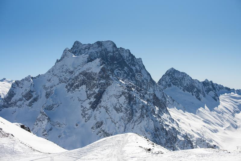 Winter mountains with snow and blue sky in nice sun day. Ski resort and sport concept. Caucasus Mountains, region Dombay. View. From the top of Musa Achitara royalty free stock image